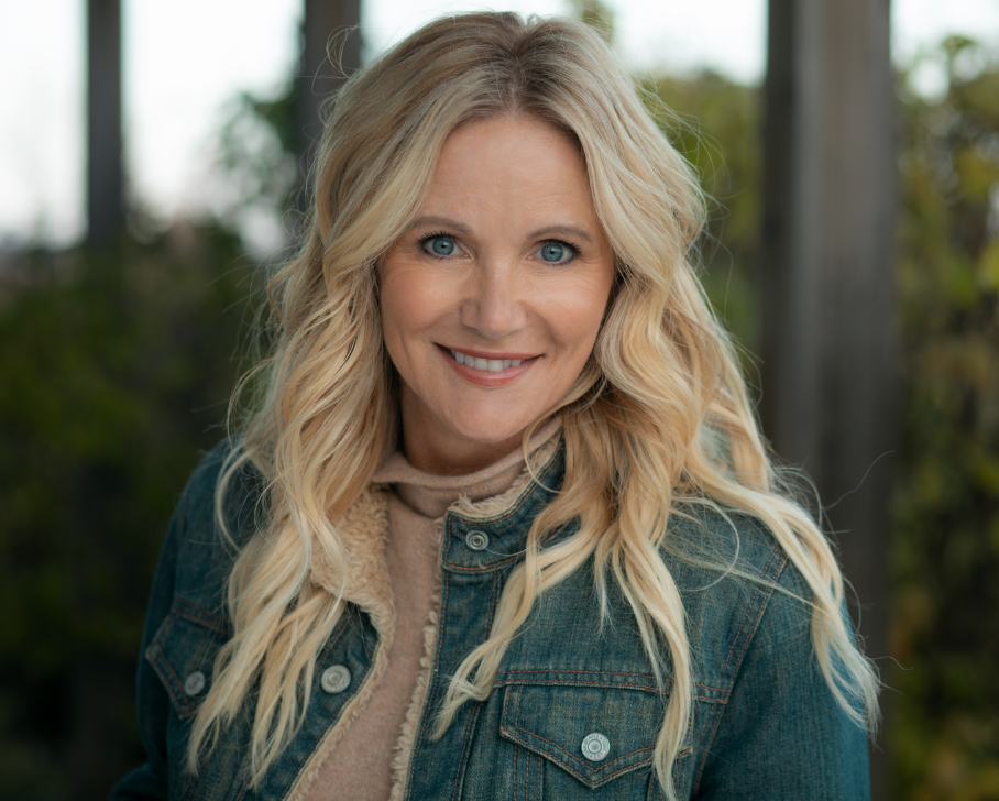 Kathryn Burgum, wearing a jean jacket and tan turtle neck smiles forward